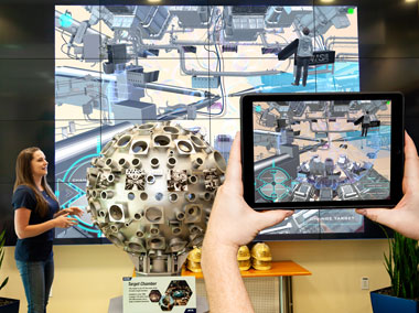 A computer tablet transforms a scale model of NIF's target chamber into augmented reality (AR) and VR views, which are also displayed on a giant video wall inside NIF's lobby.