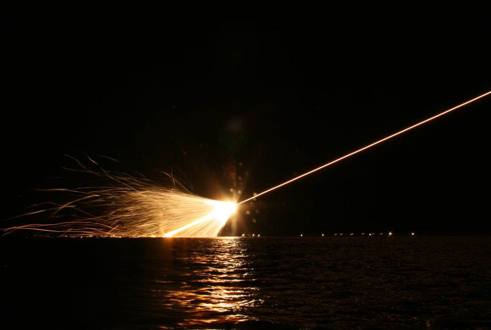 Missile explodes above water at night