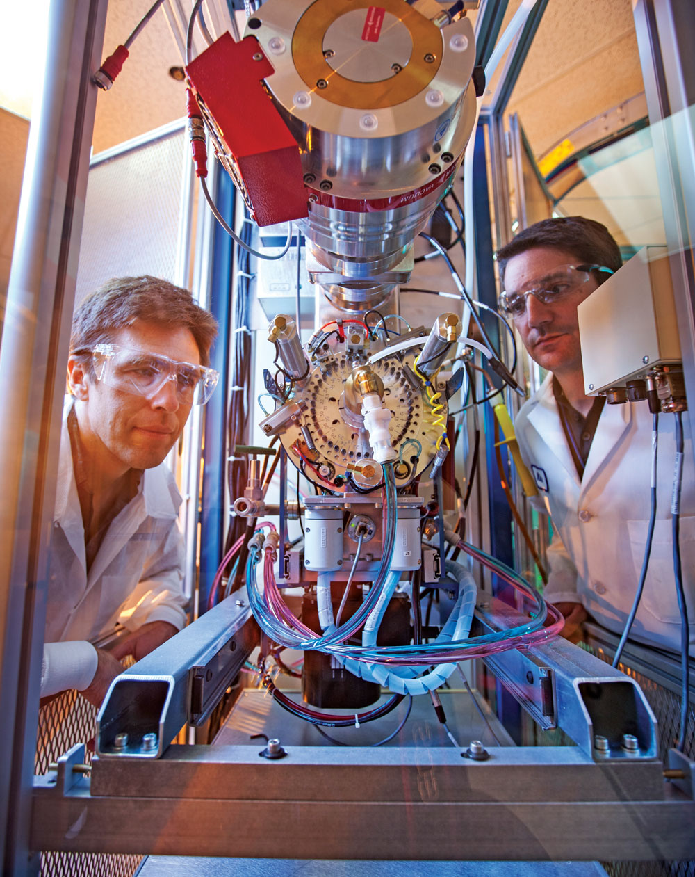 Two scientists peer into an accelerated mass spectrometry unit.