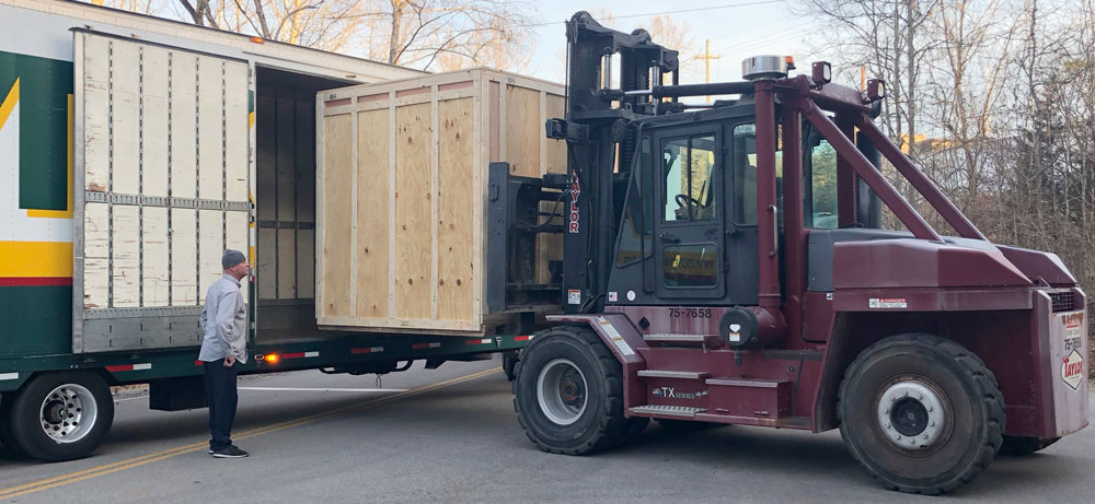 The crated detector is unloaded from a semi-truck.