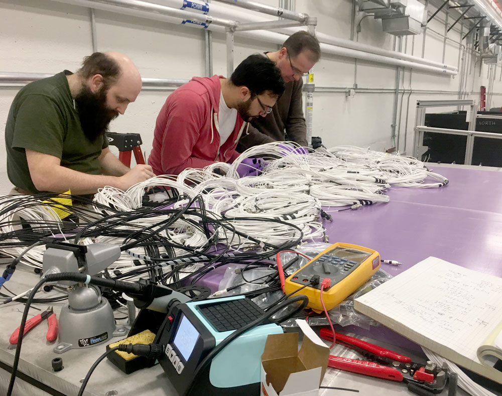 Three men work at a table covered in wiring, tools, and other components of the detector.