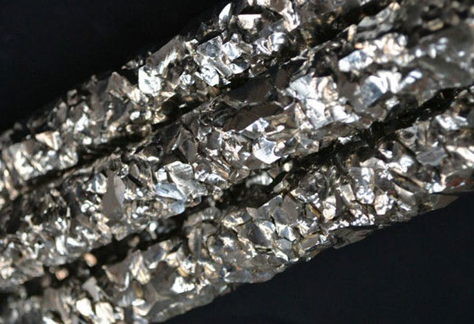 A close-up view of three columns of shiny, craggy zirconium.