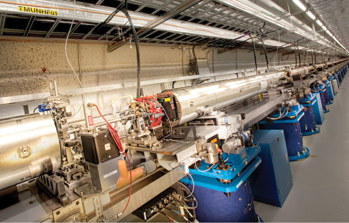 The SLAC National Accelerator Laboratory's Linac Coherent Light Source (LCLS)—the world's most powerful x-ray free-electron laser (XFEL)—is the first machine of its type to probe matter with hard x rays. In the LCLS Undulator Hall (shown here), short pulses of electrons travel back and forth through a 100-meter-long stretch of alternating magnets. The process produces the extremely bright x rays that are used to image structural changes in complex biomolecules, such as proteins.