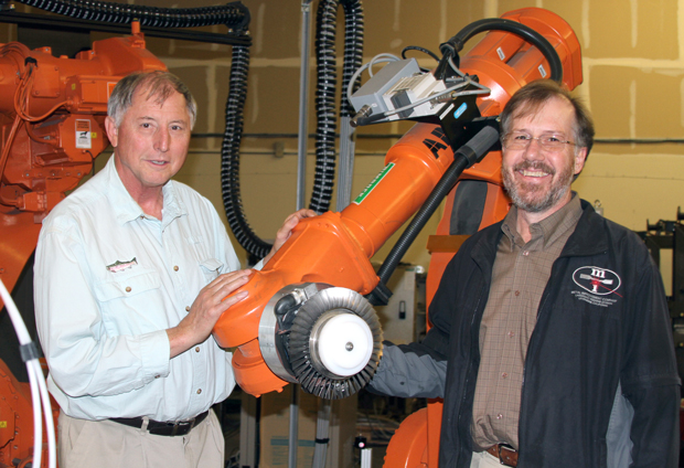 Lloyd Hackel (left) and Brent Dane stand with a robot used in laser peening to strengthen critical parts for aviation and other industries. The duo successfully commercialized a laser peening technology—marketed as the Lasershot Peening System—used around the world in airplane fuselages and turbines, as well as in turbines for electric power generation. (Photograph by Julie Russell.)""