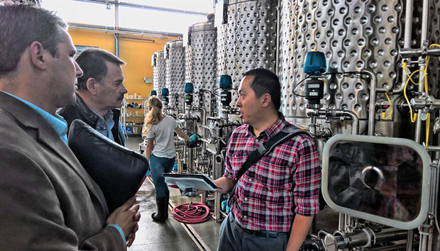 Livermore researcher Congwang Ye (left) visits with professors at the University of California at Davis at their pilot-scale brewery to learn about fermentation tank operations as part of his adaption of a microcapsule technique for trapping carbon dioxide (CO2) to commercial breweries. Ye hit on this application through his participation in Energy I-Corps.