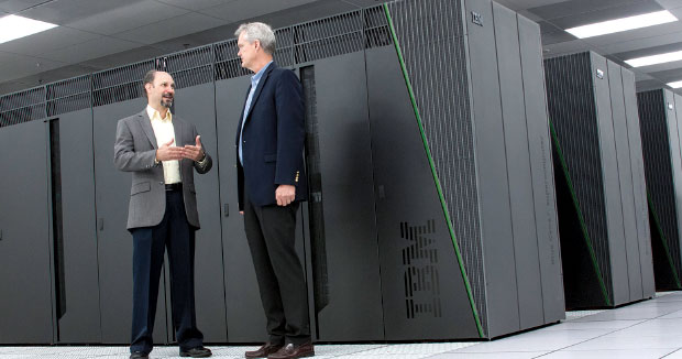 HPCIC Director Frederick Streitz (left) meets with Doug East, the Laboratory's chief information officer, in front of the Laboratory's Vulcan supercomputer. This IBM BlueGene/Q system can process 5 quadrillion floating-point operations per second. (Photograph by Laura Schulz.)