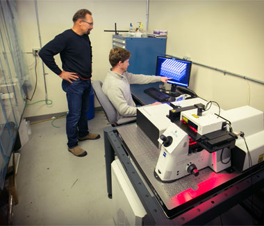 Livermore scientists James Oakdale (seated) and Juergen Biener examine a three-dimensional printed foam design before fabricating it using the Laboratory's Nanoscribe Professional GT printer.