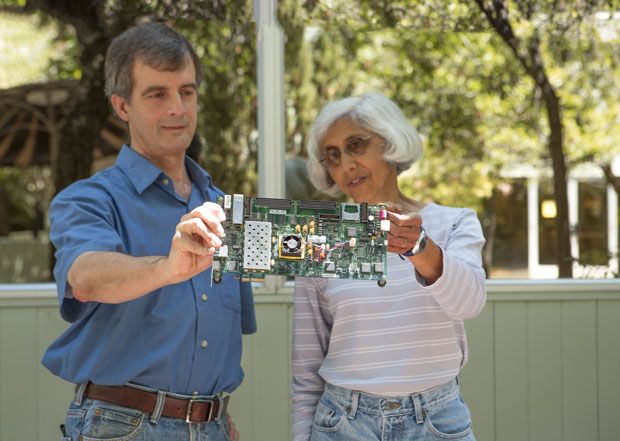 Computer scientists (from left) Scott Lloyd and Maya Gokhale inspect a  memory unit emulator on a circuit board. (Photo by Lanie L. Rivera.)