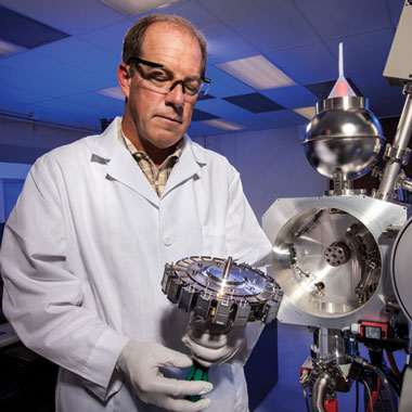 Borg is shown holding the sample wheel of a thermal ionization mass spectrometry system, which the cosmochemistry team uses to measure isotope ratios.